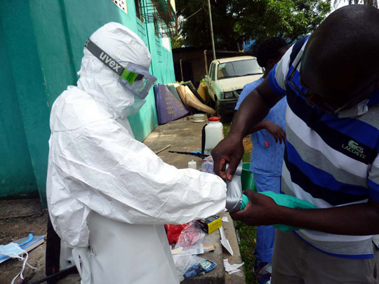 Volunteers of International Medical Corps (IMC) suiting up in personal protective equipment (photo by J.M. Souers)